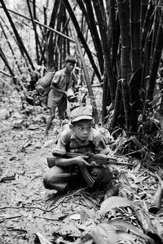 1973 - Two teenage Viet Cong soldiers at camp  near Cai Lay, one carrying a captured U.S. automatic weapon, the other an